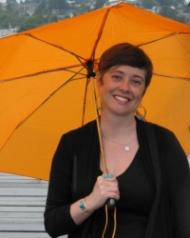 Heather D. Evans, white woman smiling holding brightly colored umbrella