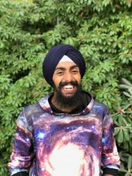 Jasmair smiling broadly, wearing a turban and brightly-colored shirt, standing in front of green foliage.