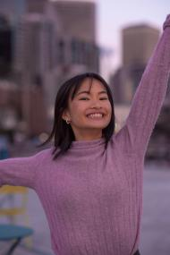 Katherine, Asian woman, short brown hair with bangs, wearing a pink sweater, smiles at the camera with her left arm raised up and her right arm to the side in front of out-of-focus buildings.
