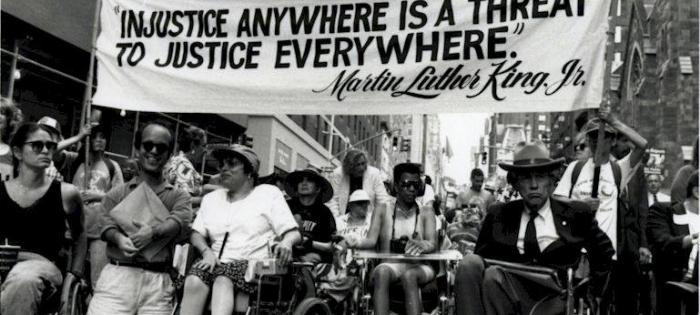 """1993 march in New York City. At front are Paul Miller, Judy Heumann, Justin Dart. Holding a sign that says: """"Injustice anywhere is a threat to justice everywhere."""""""