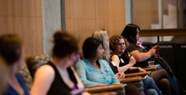 audience members seated looking at person speaking into mic at UW PWDS symposium 2015